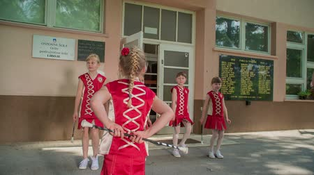 pom : Girls are really happy dancing in front of the school. They are wearing red costumes and are practising with majorette sticks.