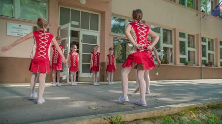 pom : Girls start practising the routine. This is taking place outside the school.