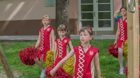 pom : Girls are practising dancing on the school yard. Theyre holding red and yellow pom-poms.