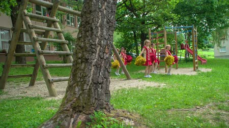 детская площадка : Cheerleaders are holding pom-poms in their hands. Theyre practising their choreography in the school yard.