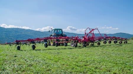 preciso : The rotary rakes are huge and they are moving up in the air. The farmers need to cut grass in summer time.