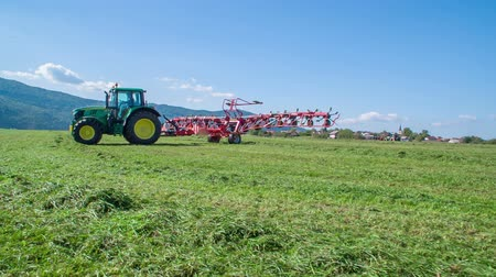 ancinho : Agricultural machinery is moving fast. A tractor is driving across the field.