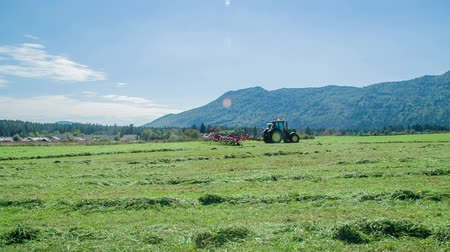 tudo : Farmers are driving across the meadow and are turning grass around so that it will be dry on all sides.