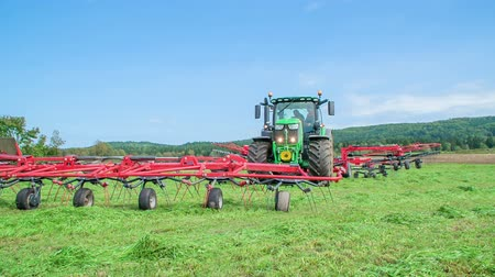 újra : A tractor is standing still and rotary rakes are not moving. Farmers have a short break before they start cutting grass again.