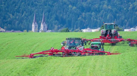熊手 : Two tractors are driving on a grass field and are cutting grass. The day is sunny and warm. There is a village with a church in the background. 動画素材