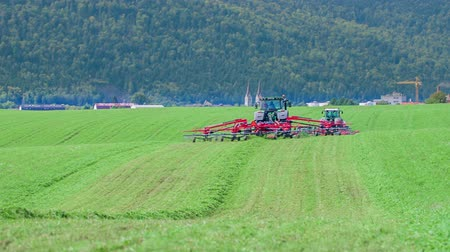 döner : Two red tractors need to cut grass with their agricultural machinery on a big green grass field.
