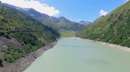 Lots of hills are surrounding the river. The water is light blue. Its summer time and the sun is shining.