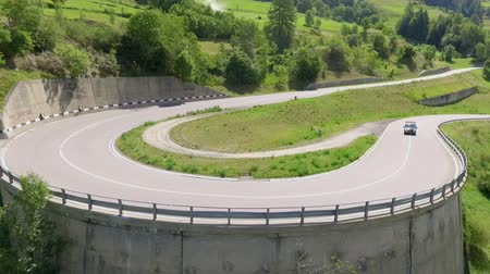 parreira : A big sharp curve. A car is driving uphill into a curve. The landscape is green during this time of year.