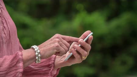 tárcsáz : A woman is typing something on the touch screen phone.