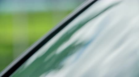 tárcsázás : A young woman is touching the surface of a car window and she is checking if it is clean enough. Stock mozgókép
