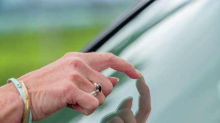 tárcsázás : A young woman is checking the cleanliness of a car window. She is trying to get rid of something on it.