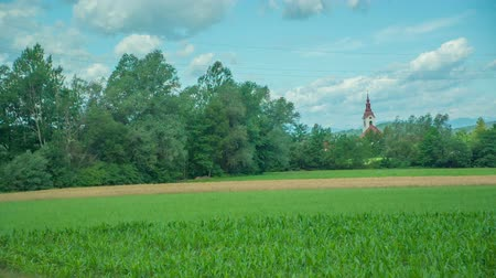 pecsét : A car is passing a beautiful nature when driving on a highway. There is also a church tower seen in the background.