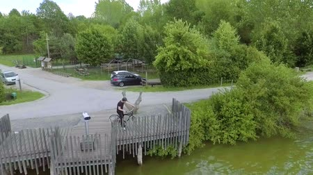 slovenya : A young man sits down on his bicycle and drives away. He is going to drive along the river. Stok Video