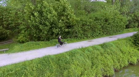 A young man is enjoying the ride with a bicycle around the lake and he is also looking around.