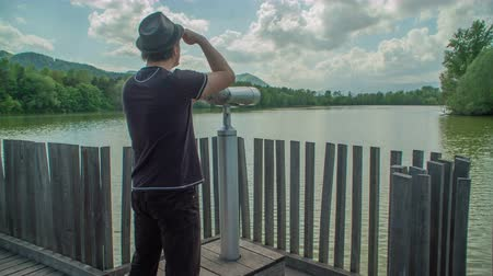 hops : A young man is standing on the side of a lake in Slovenia and he is observing the view through binoculars.