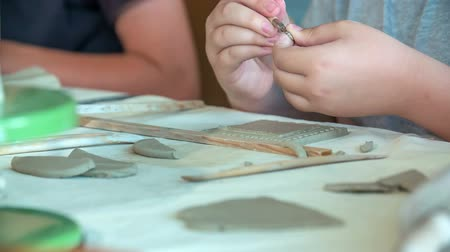 Young school children are using different tools and brushes when they are making something from clay in their art class.