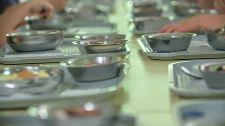 biblioteca : Pupils are having lunch in their school canteen. They are sitting next to each other. Stock Footage