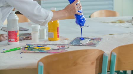 детская площадка : A teacher in art class is putting a yellow and blue colour on the pallet for the pupils. They will paint paintings. Стоковые видеозаписи