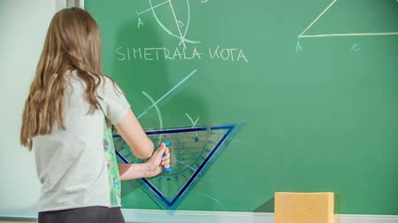 A young student is drawing something on a blackboard with a ruler. They are having a math class. Stock Footage