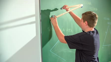 элементы : A young boy is trying to draw a circle with a pair of compasses on a blackboard in his math class.