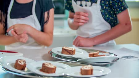 Pupils are enjoying their cooking class. Today, they have baked a chocolate cake with some cream. Stock Footage