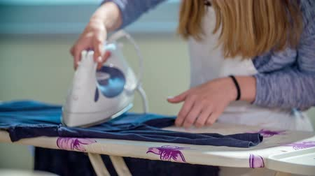 konu : A girl is ironing clothes on the ironing board in home economics class. Students are really enjoying it.