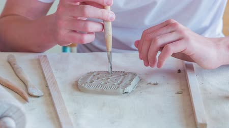 konu : Students in art class are using different tools and equipment for moulding clay.