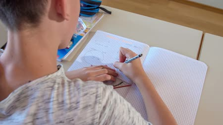 učitel : A boy is using a ruler and a pencil to draw a straight line in his notebook in his math class.