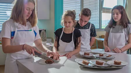 subject : Classmates are watching the girl when shes cutting the cake and distributing it on plates for her classmates. Stock Footage