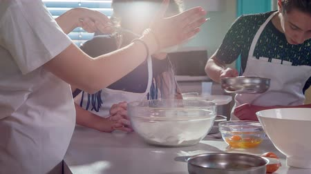 konu : Kids are busy making a dessert at home economics class. One of them is putting flour through a sifter and the others are preparing the dough.