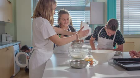 a diákok : Kids are preparing some dessert at home economics class. One of them is taking a white bowl and is putting flour through a sifter into another bowl. Stock mozgókép