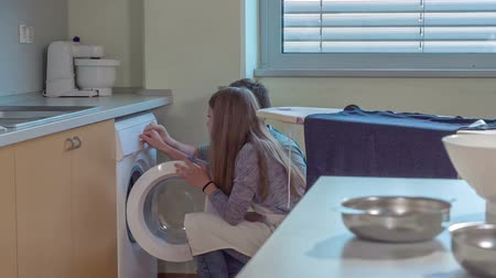 Girl is helping her classmate with turning on the washing machine. They are having home economics class.