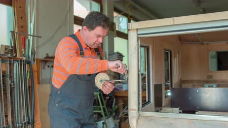 A middle-aged woodworker is using two types of wrenches to adjust the car mirror on a vintage car that he is designing in his workshop at home.