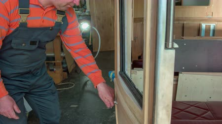 sander : A man is carefully checking the surface of the door on a brand new wooden car that he is designing. He is putting in a lot of effort.