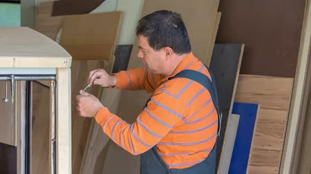 sander : A middle-aged woodworker looks very dedicated. He is trying to build a new vintage wooden car.