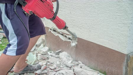 Male holding jackhammer and slowly, but effectively, demolishing concrete wall with jackhammer.
