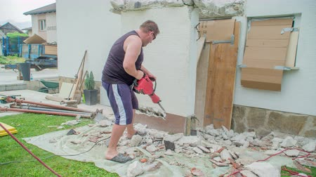 kőműves : Young man is using very heavy but very useful concrete demolition hammer to make holes into concrete wall. Surroundings is in a total mess. Stock mozgókép