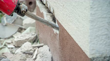 penetrating : Jackhammer`s chisel slowly penetrating into concrete brick and making a hole.