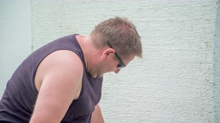 demolishing : Young man wearing sunglasses and working hard with jackhammer. Vibrations are transmitting from jackhammer to a man and vibrations are visible on his arms. Stock Footage