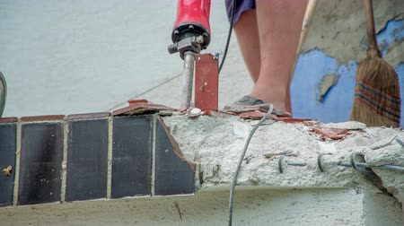 demolishing : Worker removing smaller pieces of dark brown ceramic tiles with concrete demolition hammer. Stock Footage