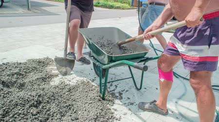 Man mixing concrete mixture and water in a green metal wheelbarrow with a hoe. Two other men are resting and observing the activity.