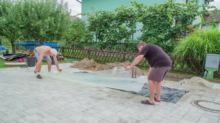 каменная кладка : Men carefully placing transparent plastic foil to the paving blocks to protect them from the dirt and possible damages.