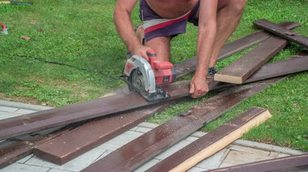 helmets : Elderly man cutting dark brown wooden board up into stripes wit a help of a handy circular saw.
