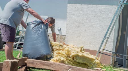 renovação : Men carefully putting preserved glass wool into black plastic bag. Younger man is holding a bag and the elder one is stuffing wool in a bag.