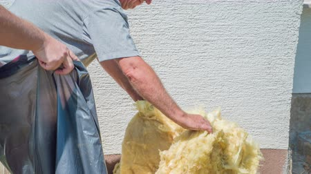 pedreiro : Elder man is carefully tearing apart glass wool and the other man is holding a black plastic bag. They will stuff glass wool into bag. Vídeos