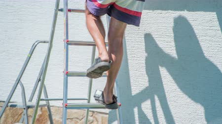 demolishing : Elderly man wearing shorts going down the ladder with caution.