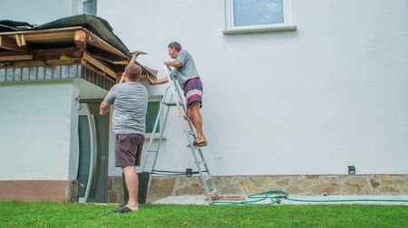 demolishing : Young man demolishing jutting roof with pickaxe. Elderly man is climbing the ladder to help younger guy. Stock Footage