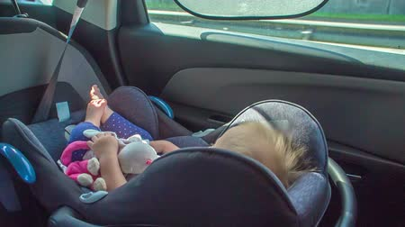 A girl is peacefully sleeping on a child safety seat when driving in a car on a highway. Stock Footage