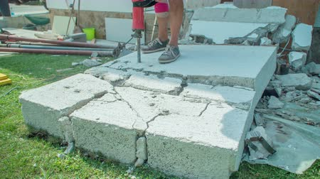 Man demolishing concrete wall with powerful jackhammer to smaller pieces. Man`s knee is bandaged because of serious injury. Dostupné videozáznamy