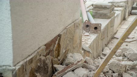 penetrating : Jackhammer`s chisel slowly penetrating through concrete wall that is covered with decorative bricks. Stock Footage